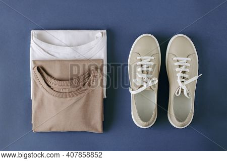 Neatly Folded Two T-shirts And Sneakers Made Of Natural Materials In White And Beige Colors On A Blu