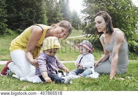 Two Friend Women Enjoying A Picnic In A Beautiful Sunny Day With Their Little Daughters - Women Sitt
