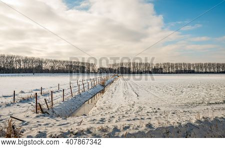 Dutch Winter Landscape With Ditch And Fences. The Water In The Ditch Is Partially Frozen. The Photo