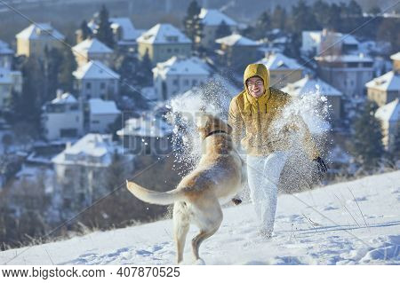 Young Man With Dog In Winter. Pet Owner With His Labrador Retriever Playing In Snow Against City. Pr