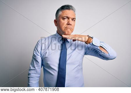 Middle age handsome grey-haired business man wearing elegant shirt and tie cutting throat with hand as knife, threaten aggression with furious violence