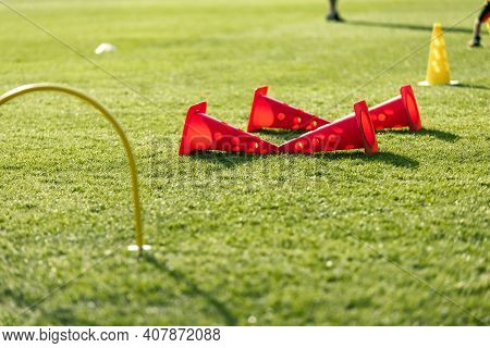 Sports Training For Kids. Training Equipment On Grass Pitch. Row Of Plastic Training Cones On Field.