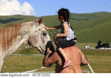 Norcia (pg), Italy - May 25, 2015: A Child Caressing A Horse In The Country Near Castelluccio Di Nor
