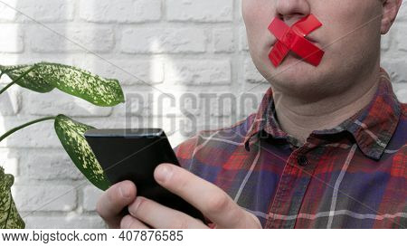 Men With A Red Sticky Tape Taped Their Mouths, A Man With A Smartphone In His Hands With Sticky Tape