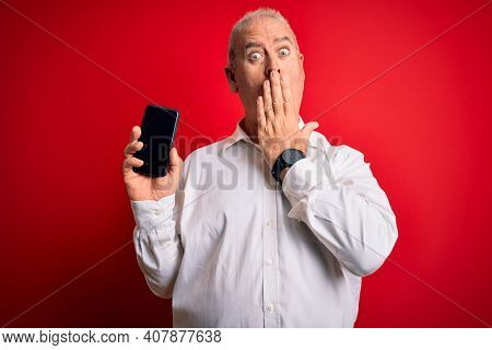 Middle age hoary man holding smartphone showing screen over isolated red background cover mouth with hand shocked with shame for mistake, expression of fear, scared in silence, secret concept