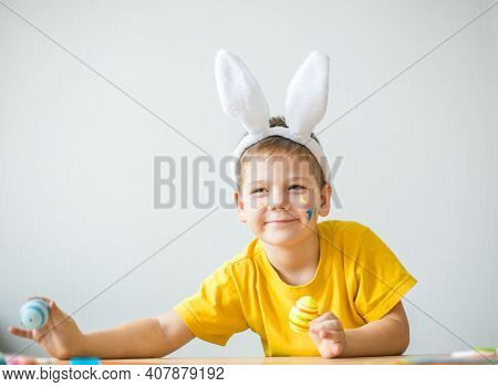 Portrait Of Smiling Boy With Bunny Ears Keeping Colored Eggs For Easter In Art Studio, Copy Space. P
