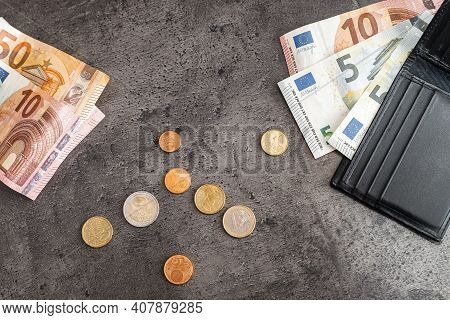 Close Up Of Money Banknotes, Coins And Black Wallet. Euros On Dark Background