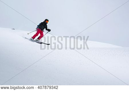 A Freerider Skier In Red Pants With A Rockzack Rides Down A Snowy Slope In Cloudy Weather. Womens Fr