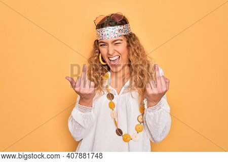 Young beautiful blonde hippie woman with blue eyes wearing sunglasses and accessories Showing middle finger doing fuck you bad expression, provocation and rude attitude. Screaming excited