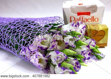 Moscow, March, 2020. Bouquet Purple Eustoma Lisianthus Flowers, Gift Box Love, Raffaello Candy On Wh