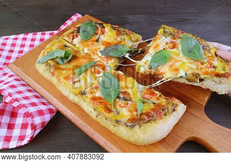 Slice Of Mouthwatering Pesto Veggie Pizza With Stretching Cheese Being Taken From Breadboard