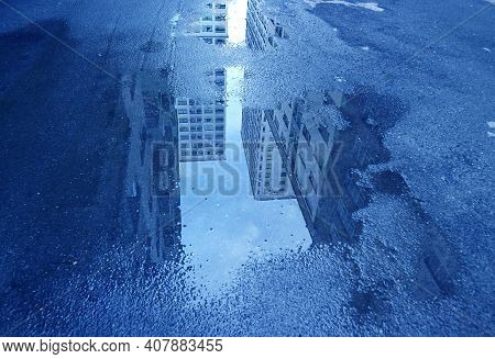 Pop Art Style Blue Colored High Buildings After Rain Reflecting On The Puddle