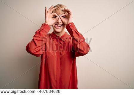 Young beautiful business blonde woman with short hair standing over isolated background doing ok gesture like binoculars sticking tongue out, eyes looking through fingers. Crazy expression.