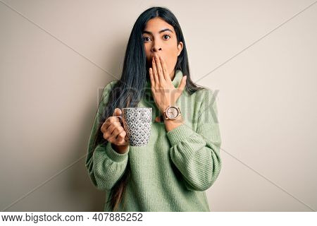 Young beautiful hispanic woman drinking a cup of hot coffee over isolated background cover mouth with hand shocked with shame for mistake, expression of fear, scared in silence, secret concept
