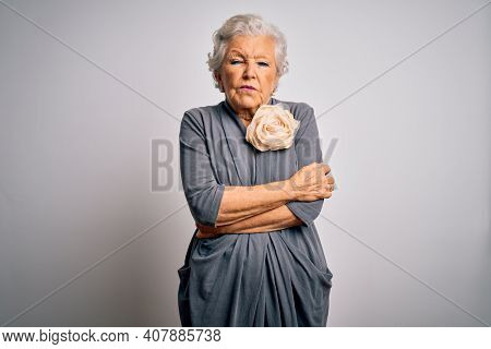 Senior beautiful grey-haired woman wearing casual dress standing over white background shaking and freezing for winter cold with sad and shock expression on face