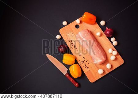 Fresh Pork Fillet On Cutting Board On Dark Background. Raw Colorful Peppers, Champignons, Purple Oni