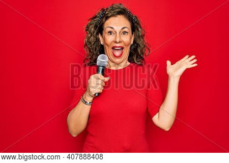 Middle age senior singer woman singing using music microphone over red background very happy and excited, winner expression celebrating victory screaming with big smile and raised hands