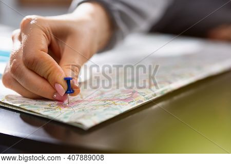 Female Hand Holding Pushpin Showing The Location Of A Destination Point On A Map. Travel Destination