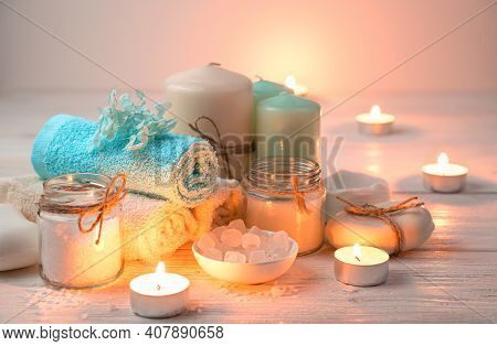 Candles, Towels, Soap And Salt On The Background Of Burning Candles.