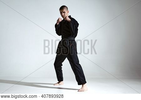 Angry Guy Trainer In Black Kimono Fighter Posing In Karate Stance On Studio Background With Copy Spa