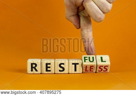 Restless Or Restful Symbol. Businessman Turns Wooden Cubes, Changes The Word 'restless' To 'restful'