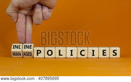 Inline Or Managed Policies Symbol. Businessman Turns Wooden Cubes, Changes Words Inline Policies To
