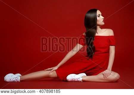 Sport chic style. Beautiful brunette girl posing at studio in red dress and white sneakers. Red background.