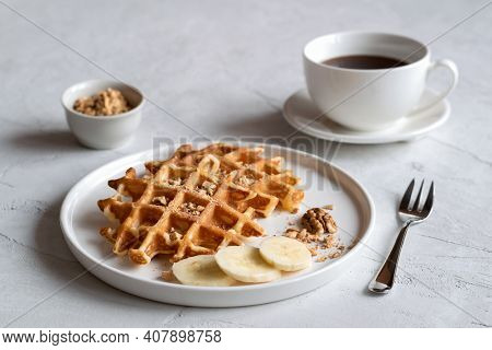 Traditional Belgian Waffles With Slices Of Fresh Banana, Ground Nuts And A Cup Of Coffee On A Concre