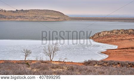 winter scenery of mountain lake at foothills of Rocky Mountains, partially frozen Horsetooth Reservoir - a popular recreational area in northern Colorado