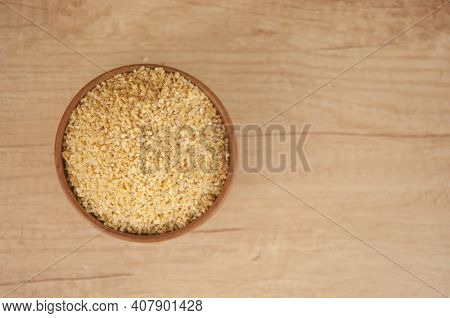 wheat groats in a wooden bowl on a wooden table background. Top view