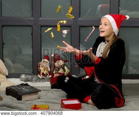Happy Girl In Santa Hat Throwing Up Candy Sweets. Joyful Teenage Girl Wearing Jumpsuit Sitting On Fl