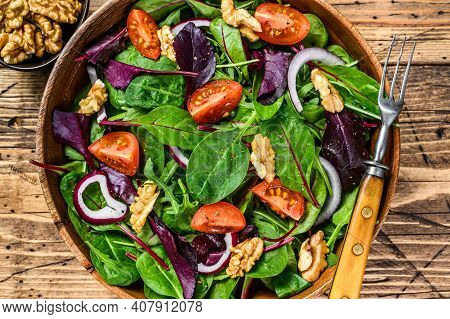 Fresh Vegetable Green Salad With Leaves Mangold, Swiss Chard, Spinach, Arugula And Nuts. Wooden Back