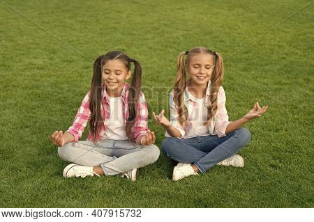 Practicing Mudras During Meditation. Happy Children Do Meditation On Green Grass. Small Girls Enjoy