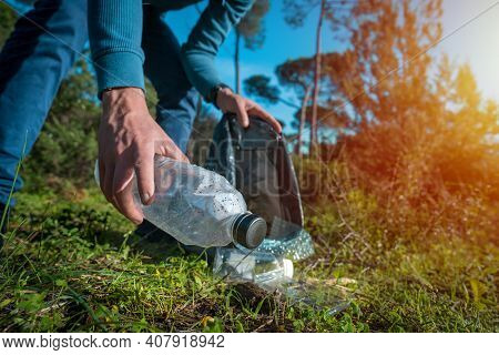 Man Cleaning-up The Forest Of Plastic Garbage. Nature Cleaning. Volunteer Picking Up A Plastic Bottl