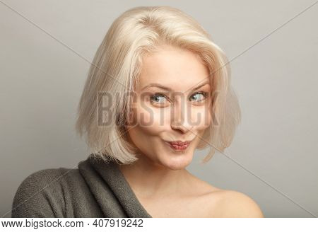 Close Up Attractive Blond Hair Woman With Cunning Smirk, Constrain Laugh, Isolated On Gray Backgroun