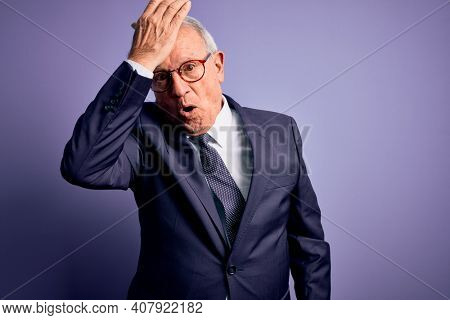 Grey haired senior business man wearing glasses and elegant suit and tie over purple background surprised with hand on head for mistake, remember error. Forgot, bad memory concept.