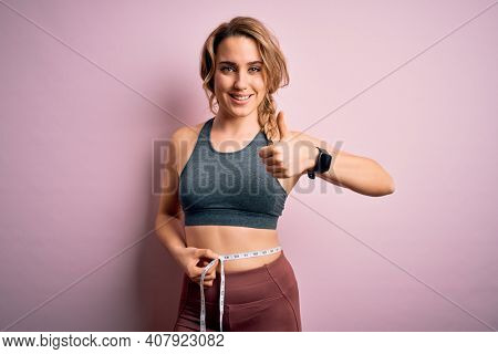 Young blonde sportswoman wearing sportswear controlling weight using tape measure on waist happy with big smile doing ok sign, thumb up with fingers, excellent sign