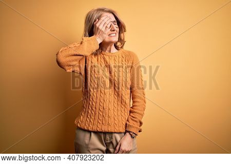 Middle age beautiful blonde woman wearing casual sweater and glasses over yellow background Yawning tired covering half face, eye and mouth with hand. Face hurts in pain.