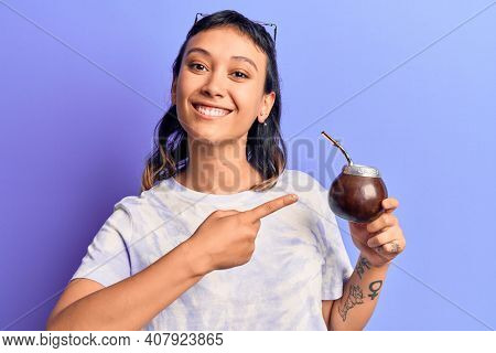 Young woman drinking mate infusion smiling happy pointing with hand and finger