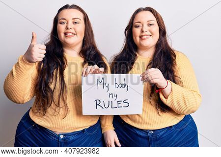 Young plus size twins holding my body my rules banner smiling happy and positive, thumb up doing excellent and approval sign