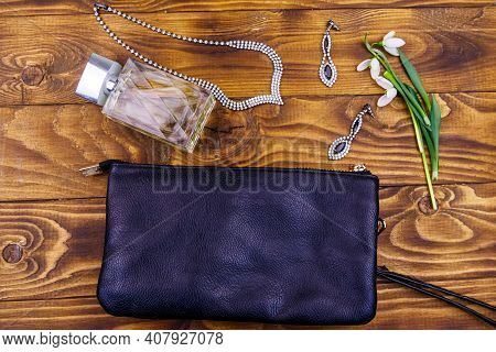 Women Accessories On Wooden Background. Clutch Bag, Bottle Of Perfume, Necklace, Earrings And Snowdr