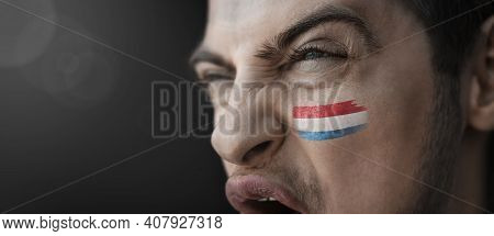 A Screaming Man With The Image Of The Luxembourg National Flag On His Face