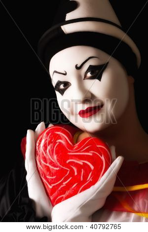 Beautiful pierrot clown in love with a red candy heart