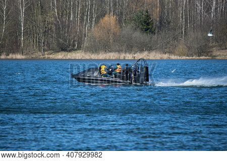 A Black Lifeboat With An Air Motor Floats Fast On The Lake. Training Of Rescuers Of Belarus In Early