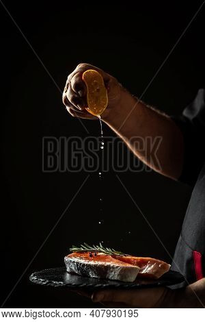Man Squeezing Lemon On Salmon Steak, Adding Sour Flavor To Fish. On Black. Vegan Cuisine, Clean Food