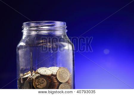 Glod coins in jar on blue background