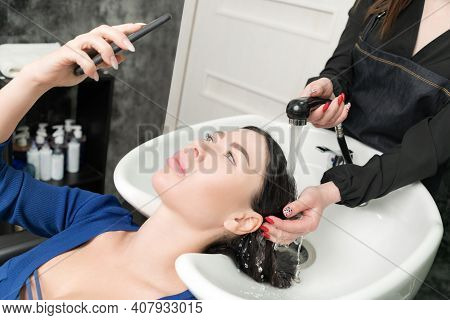 Client Looks At Phone While Hairdresser Is Busy Washing Her Hair At Beauty Salon. Hairstylists Hands