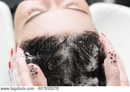 Hairdressers Hands Wash Long Hair Of Brunette Woman With Shampoo In Special Sink For Shampooing In B
