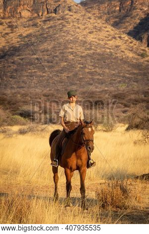 Smiling Brunette On Horseback With Hills Behind