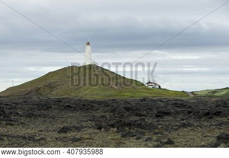 The Photo Shows A Panoramic View Of A White Lighthouse On Iceland